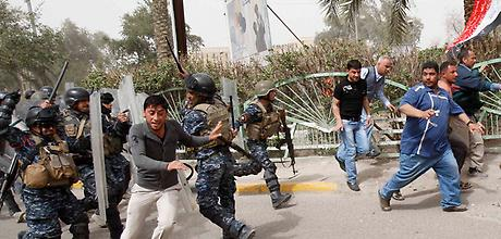 Riot policemen disperse protesters during a demonstration in Basra